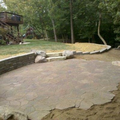 Mega arbel irregular paver patio with stone walls.