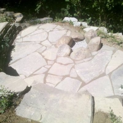 Flagstone patio surrounding granite boulder fire pit